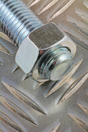 Metal fastener – A view of a nut and bolt laying on a chequered plate