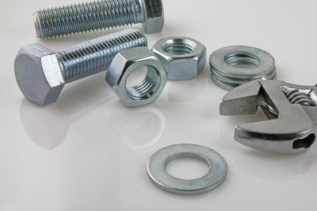 Metal fasteners – A view of nut,bolts, washers and adjustable wrench on a white reflective background Banque d'images