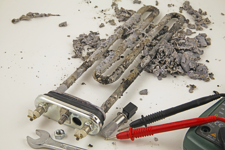 Domestic appliance repair -  A  damaged washing machine heating element and a multi meter on a white surface