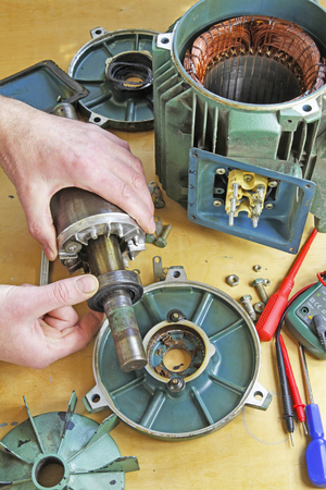 Three phase induction   motor bearing repair – A fittertechnician  removing rotor from stator  prior to changing shaft bearings