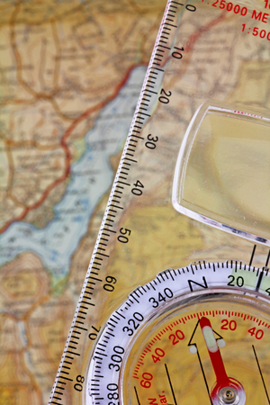 Compass and  map -  A compass with a set bearing being lined up above a map
