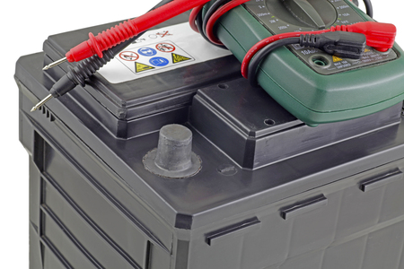 Car battery – A multi meter with its probes laying on top of a twelve volt car battery isolated on a white background