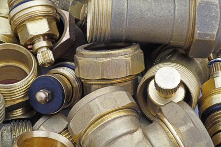 plumbers fittings and pipes –  a  plan view of brass compression fittings on a bench