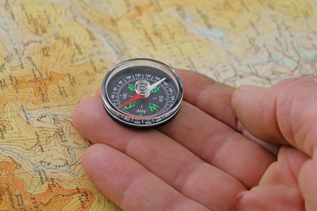 Compass and  map -  A hand holding a magnetic compass being lined up to walk on a magnetic bearing
