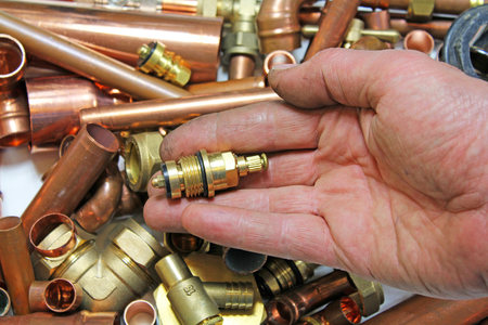plumbers fittings and pipes – a man's hand holding a tap head gear over pipes and fittings Banco de Imagens