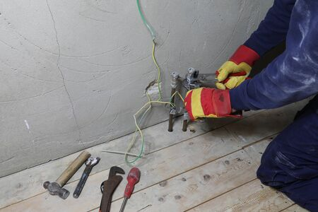 Plumber adjusting pipework with wrenches in a domestic bathroom Banque d'images