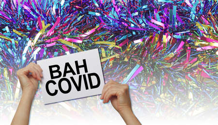 Bah Covid Concept Background – hands holding a white placard with the words BAH COVID against a graduated Christmas tinsel background with copyspace
