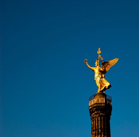 else: Side view of the golden statue of winged Victoria on top of the famous Victory Column (Siegess�ule) monument. Berlin, Germany.
