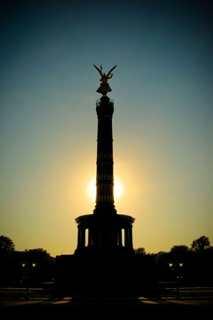sillhouette: View at sunset of the golden statue of winged Victoria on top of the famous Victory Column (Siegess�ule) monument. Berlin, Germany.