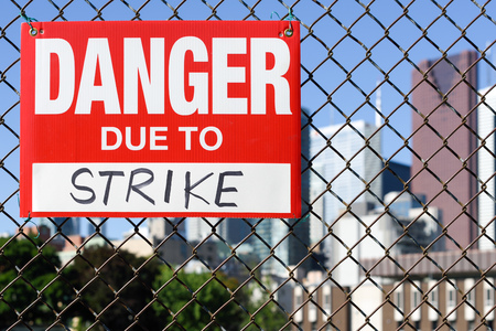 Sign danger due to strike attached on the fence in the front of the town