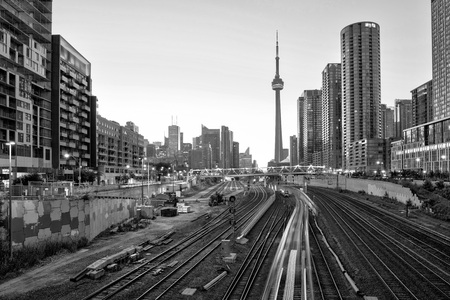 A view of Toronto downtown and CN tower in black and white over the bridge with buildings and train at sunrise Stock fotó
