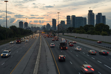 Highway  Gardiner Expressway in Toronto Ontario with tail lights and buildings at dawn before sunrise