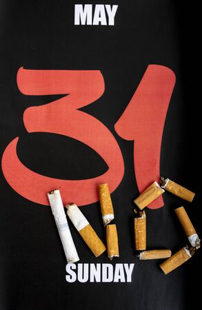 Concept image for World No Tobacco Day. Broken and burnt cigarettes lying on a calendar with the day May 31 Stock Photo