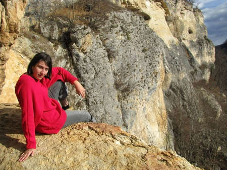 Girl; sits; smile; breakaway; height; tourism; mountains; nature; march; active rest; pensive; beauty; landscape; type; background; Caucasus; relief; landscape