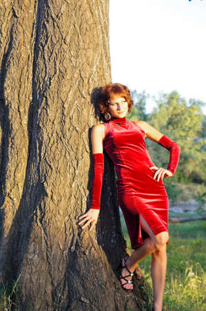 The girl in an evening red dress on the nature photo