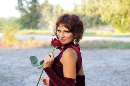 The girl in a red dress with a rose Stock Photo - 16271332