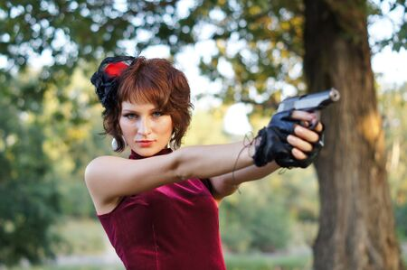 girl with gun on nature Stock Photo - 19647816