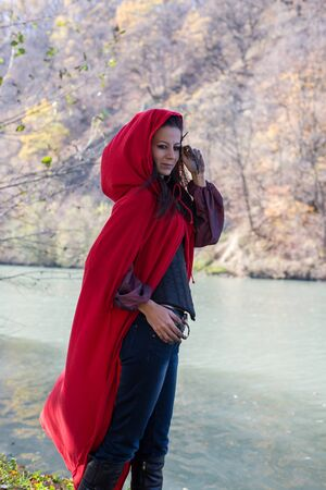 role models: Girl in a red cloak in the lap of nature Stock Photo