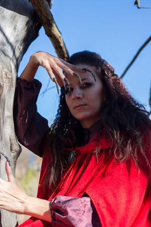 cloak: Girl in a red cloak in the lap of nature Stock Photo