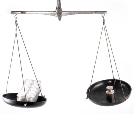 balanza de laboratorio: Equilibrio de laboratorio con la p�ldora aislado en fondo blanco Foto de archivo