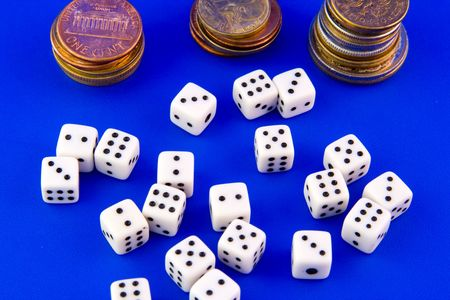 Small dices and coins isolated on blue background photo