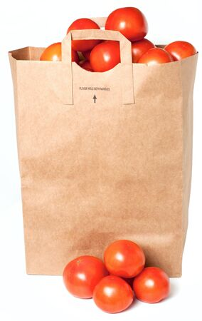 Paper shopping bag with tomatoes isolated on white background photo