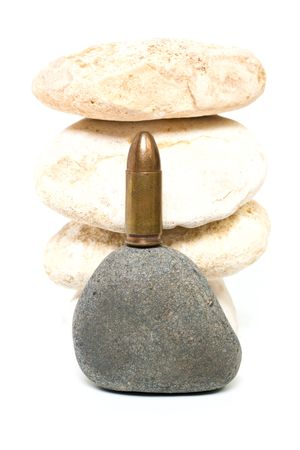 Bullet in front of stones pyramid isolated on white background photo