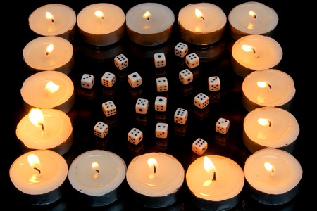 Small dices and candles isolated on black background photo