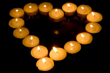 Heart of candles isolated on black background Stock Photo - 8437142