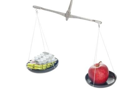 balanza de laboratorio: Balanzas de laboratorio con la p�ldora y la manzana aislada en el fondo blanco