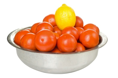 Tomatoes and lemon  in a bowl isolated on white background photo