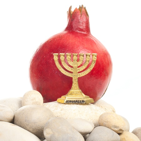 Menorah with pomegranate over a stones isolated on white background photo