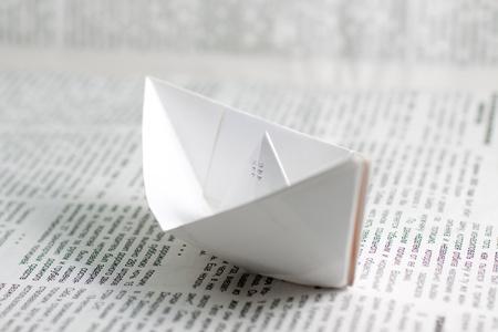Paper ship over a newspaper