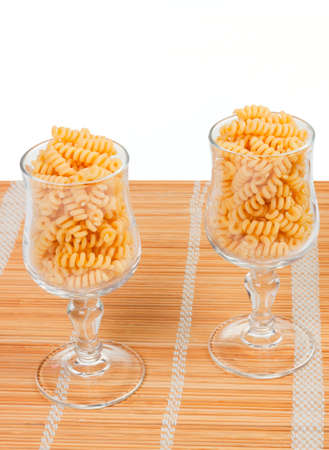 Macaroniin a glass on a straw mat isolated on white background Stock Photo - 10890533