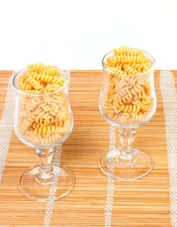 Macaroniin a glass on a straw mat isolated on white background Stock Photo - 12766996