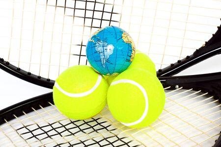 Balls and globe on tennis racket isolated on white background photo