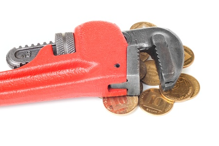 Monkey wrench on a big heap of gold coins isolated on white background photo
