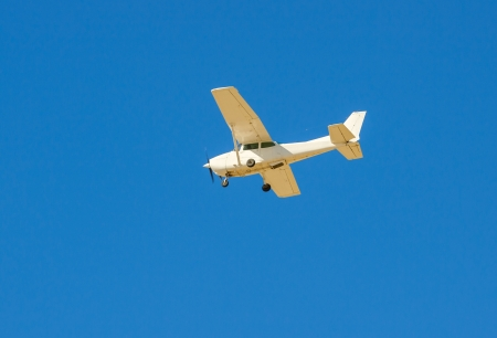 Small flying aircraft in a blue sky Stock Photo