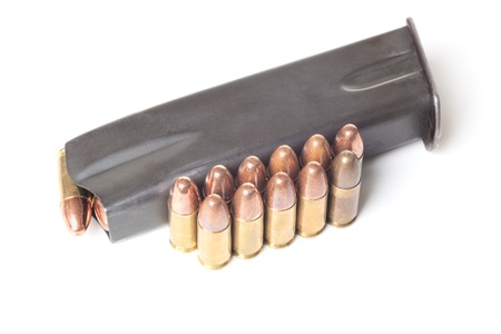 Two rows of 9mm brass bullets and gun holder isolated on white background Stock Photo - 18970197