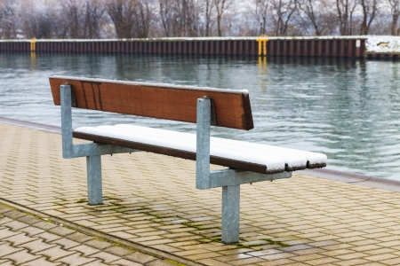 Lonely bench covered with snow on the canal bank