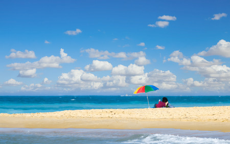 Young couple with umbrella on a beach under blue sky with clouds photo