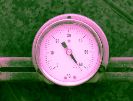 Pink round thermometer on green metallic background photo