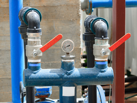 Manometer on two blue pipes with red flaps on chemical plant photo