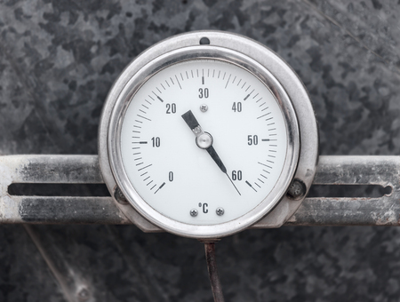 Round professional thermometer isolated on gray metallic background photo