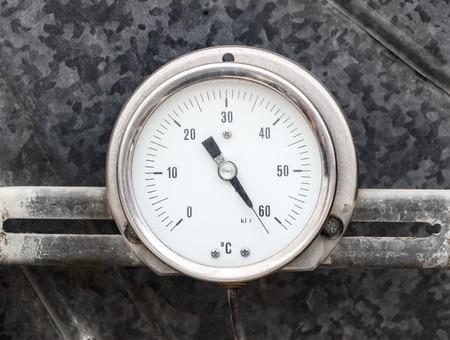 Round thermometer on gray metallic background photo