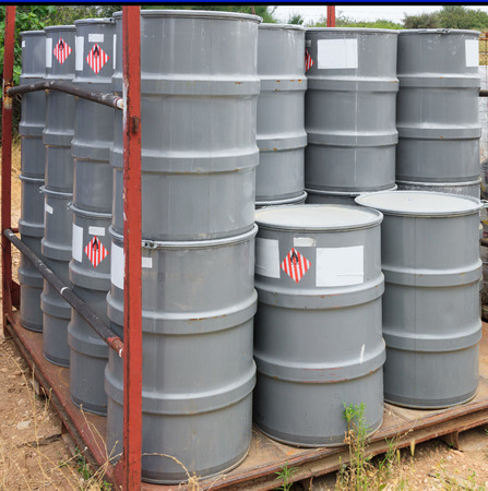 Old gray barrels on a chemical plant Stock Photo