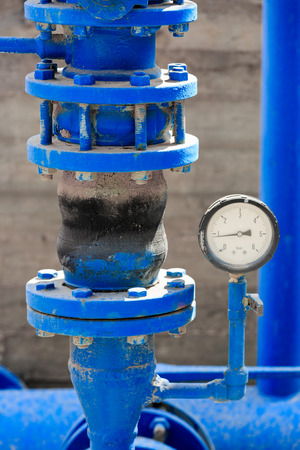Old manometer with blue pipe on chemical plant photo