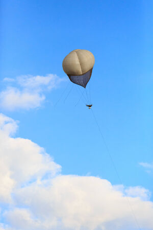 Big balloon over a white clouds in blue sky photo