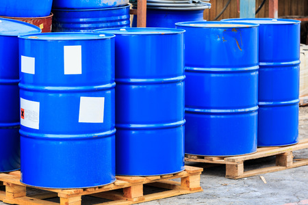 Many blue barrels standing on wooden pallets on a chemical plant