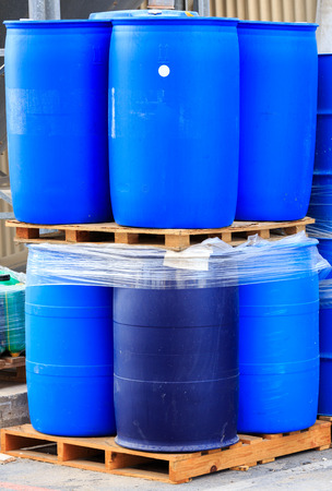 danger symbol: Vertical blue packed barrels on paletts in a chemical plant Stock Photo